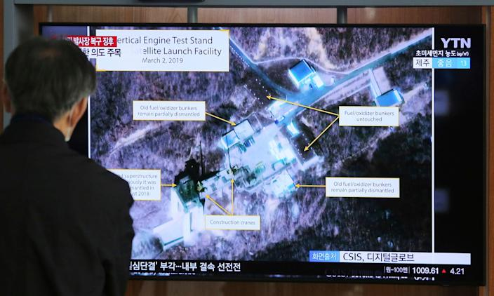 A man watches a TV screen showing a satellite launching facility in North Korea.