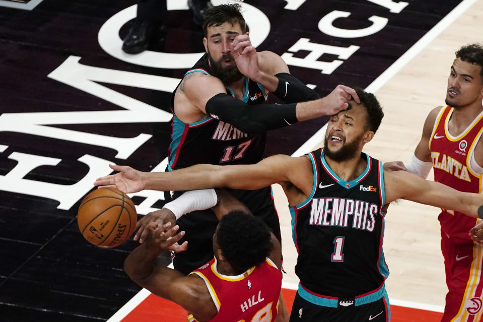 Atlanta Hawks forward Solomon Hill (18) has is defended by Memphis Grizzlies Kyle Anderson (1) and Jonas Valanciunas (17) in the second half of an NBA basketball game Wednesday, April 7, 2021, in Atlanta. (AP Photo/John Bazemore)