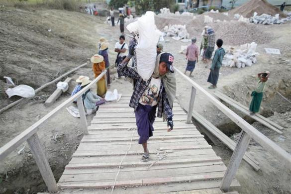 Workers carry bags at a construction site in capital Naypyitaw, January 24, 2012.
