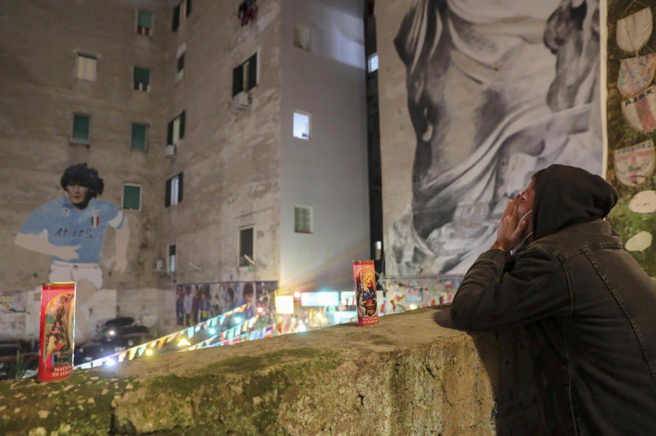 A man prays under a mural depicting soccer legend Diego Maradona, in Naples, Italy, Wednesday, Nov. 25, 2020. Diego Maradona has died. The Argentine soccer great was among the best players ever and who led his country to the 1986 World Cup title before later struggling with cocaine use and obesity. He was 60. (AP Photo/Salvatore Laporta)