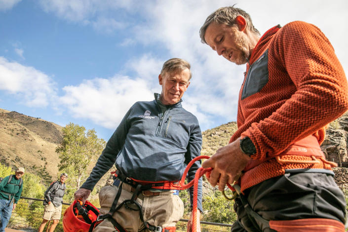 Professional climber Tommy Caldwell, front, guides U.S. Sen. John Hickenlooper, D-Colo., on a top rope route in Clear Creek Canyon Friday, Sept. 17, 2021, near Golden, Colo. The two are joining forces to draw attention to legislation aimed at curbing climate change and helping Colorado's outdoor recreation economy. (Hart Van Denburg/Colorado Public Radio via AP)