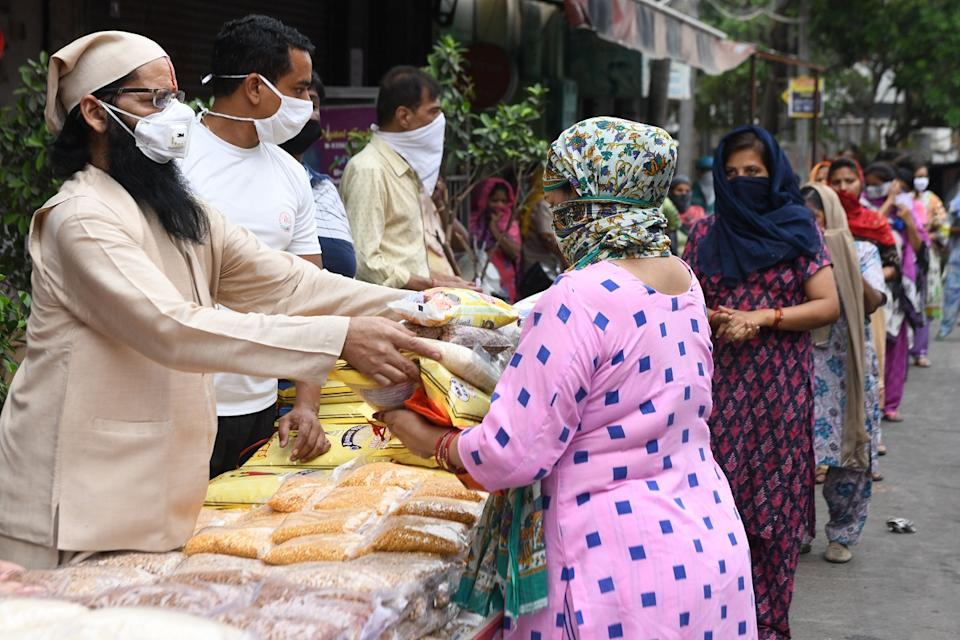 A Hindu priest along with volunteers distribute grocery items to people in need after the government eased a nationwide lockdown as a preventive measure against the COVID-19 coronavirus, in Amritsar last year. (Photo by NARINDER NANU / AFP) (Photo by NARINDER NANU/AFP via Getty Images)