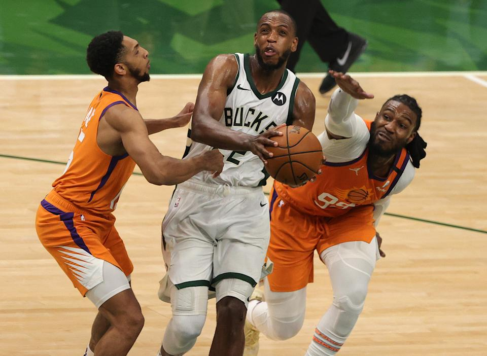 MILWAUKEE, WISCONSIN - JULY 14: Cameron Payne #15 and Jae Crowder #99 of the Phoenix Suns defend against Khris Middleton #22 of the Milwaukee Bucks during the second half in Game Four of the NBA Finals at Fiserv Forum on July 14, 2021 in Milwaukee, Wisconsin. NOTE TO USER: User expressly acknowledges and agrees that, by downloading and or using this photograph, User is consenting to the terms and conditions of the Getty Images License Agreement.  (Photo by Stacy Revere/Getty Images)