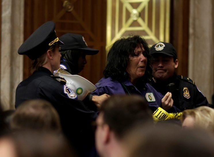 A protester is detained during Pruitt's confirmation hearing. (Photo: Joshua Roberts/Reuters)