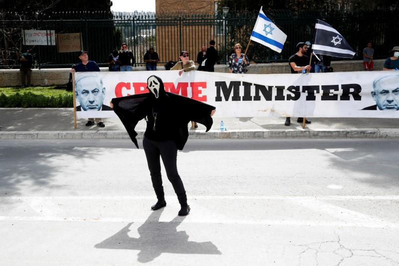 An Israeli woman wears a costume during a demonstration against PM Netanyahu's caretaker government in Jerusalem