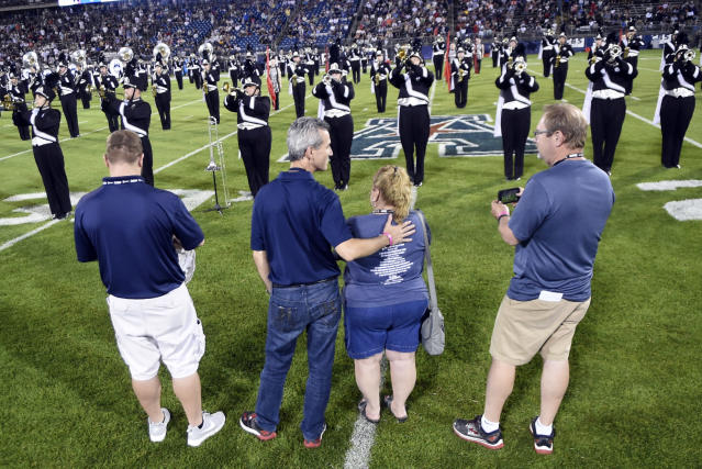 Max Schachter, second from left, the father of Alex Schachter, who was killed in the February shooting at Marjory Stoneman Douglas High School, watches the Connecticut marching band play during the halftime show dedicated to his son at an NCAA college football game, Thursday, Aug. 30, 2018, in East Hartford, Conn. From left are, Tim Goldberg, Alex's cousin; Schachter; Patti Goldberg, aunt; and Paul Goldberg, uncle. (AP Photo/Stephen Dunn)