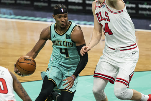 Charlotte Hornets guard Devonte' Graham (4) drives to the basket while guarded by Chicago Bulls forward Lauri Markkanen (24) during the first half of an NBA basketball game in Charlotte, N.C., Friday, Jan. 22, 2021. (AP Photo/Jacob Kupferman)