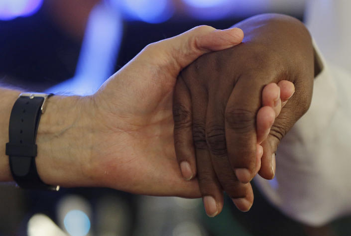 """People of different races hold hands during a singing of """"We Shall Overcome"""" at the conclusion of a service at the 16th Street Baptist Church in Birmingham, Ala., Sunday, Sept. 15, 2013. The church held a ceremony honoring the memory of the four young girls who were killed by a bomb placed outside the church 50 years ago by members of the Ku Klux Klan. (AP Photo/Dave Martin)"""