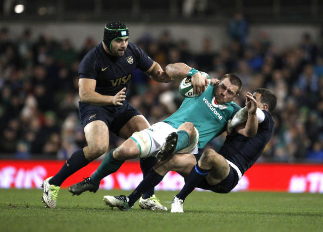 Ireland's CJ Stander, centre, is tackled by Argentina's Nahuel Tetaz Chaparro, left, and Emiliano Boffelli, right, during a rugby union international match at the Aviva stadium in Dublin, Ireland, Saturday, Nov. 25, 2017. (AP Photo/Peter Morrison)
