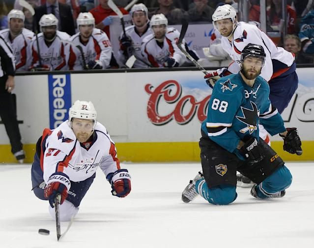 Washington Capitals' Karl Alzner, left, lunges for the puck next to San Jose Sharks' Brent Burns (88) during the second period of an NHL hockey game Saturday, March 22, 2014, in San Jose, Calif. (AP Photo/Marcio Jose Sanchez)