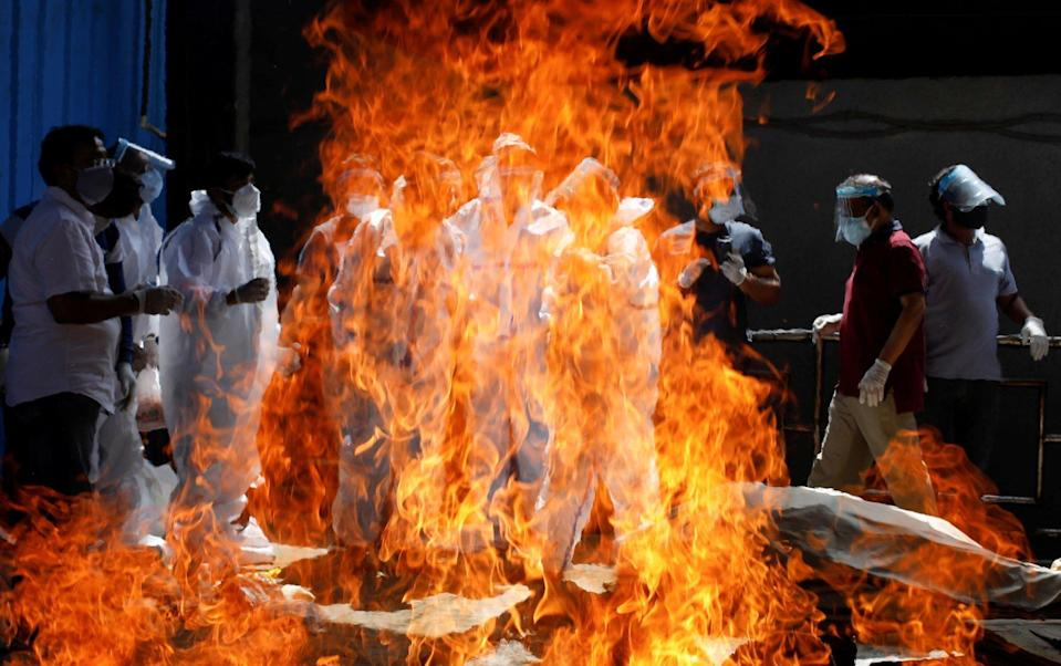 Relatives wearing personal protective equipment attend the funeral of a man who died from Covid-19 in New Delhi. Photo: Reuters