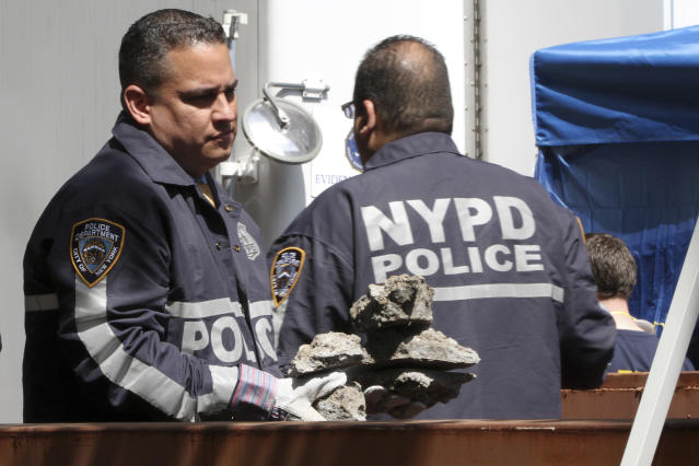 Investigators carry pieces of concrete out of a basement of a building on the corner of Wooster Street and Prince Street in the Manhattan borough of New York on Friday, April 20, 2012 during a renewed investigation into the 1979 disappearance of 6-year-old Etan Patz. Patz vanished after leaving his family's home for a short walk to his school bus stop. NYPD spokesperson Paul Browne says the building being searched for his remains is about a block from where the family lived. (AP Photo/Mary Altaffer)