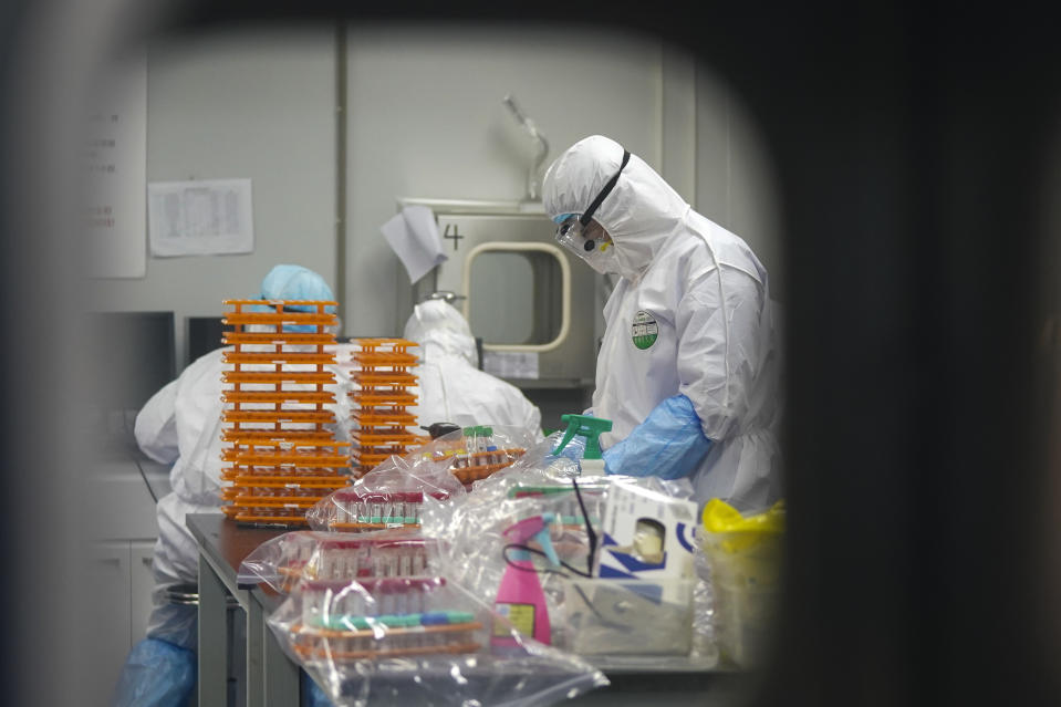This Saturday, Feb. 22, 2020, photo released by Xinhua News Agency, shows medical workers in protective suits at a coronavirus detection lab in Wuhan in central China's Hubei Province. The fresh national figures for the disease that emerged in China in December came as the number of viral infections soared mostly in and around the southeastern city of Daegu, where they were linked to a local church and a hospital. (Cheng Min/Xinhua via AP)