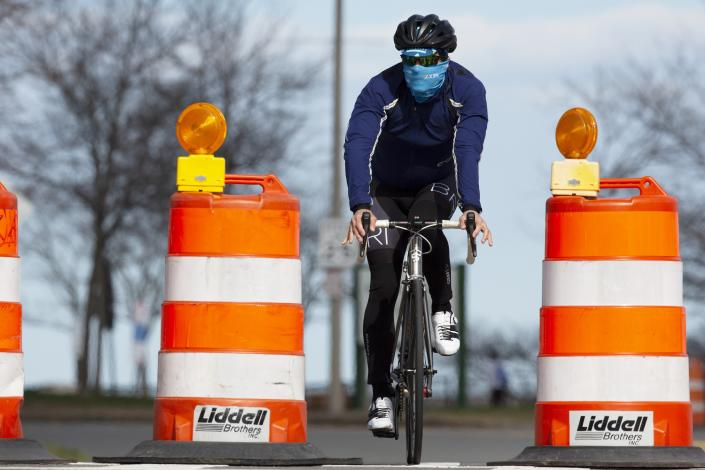 A man rides a bicycle on Day Boulevard which has been closed to traffic to reduce crowding on the adjacent sidewalk and allow social distancing, Saturday, April 11, 2020, in Boston. (Michael Dwyer/AP)