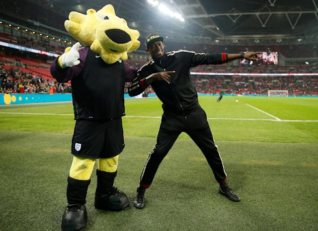 Soccer Football - International Friendly - England v United States - Wembley Stadium, London, Britain - November 15, 2018 Former sprinter Usain Bolt poses for a photograph with the mascot during half time Action Images via Reuters/Carl Recine