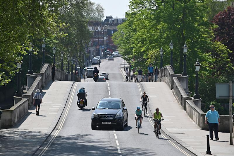 A car overtakes cyclists in Richmond, south west London on April 23, 2020 during the lockdown aimed at halting the spread of the novel coronavirus COVID-19 PANDEMIC. - Britain's health ministry on Thursday said 616 more people had died after testing positive for the novel coronavirus in hospital, taking the country's official death toll to 18,738. (Photo by JUSTIN TALLIS / AFP) (Photo by JUSTIN TALLIS/AFP via Getty Images)