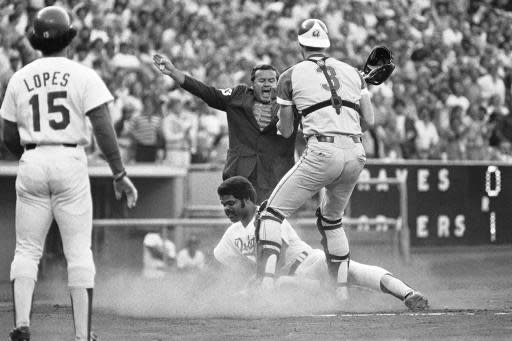 FILE - In this July 5, 1978, file photo, home plate umpire Dutch Rennert calls Los Angeles Dodgers' Reggie Smith safe under Atlanta Braves catcher Dale Murphy (3) during the first inning of a baseball game in Los Angeles. Rennert, a National League umpire from 1973 to 1992 who was known for his animated, booming strike calls, has died. He was 88. St. John's Family Funeral Home and Crematory in St. Augustine, Florida, confirmed Monday night, June 18, 2018, that Rennert died on Sunday. A cause of death wasn't given. (AP Photo/Mclendon, File)