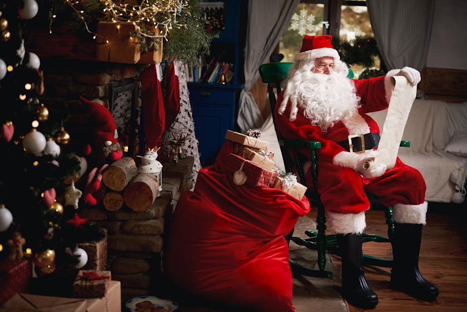 Portrait of Santa Claus, sitting in chair with sack full of presents, looking at Christmas list (Photo: Gpointstudio via Getty Images)