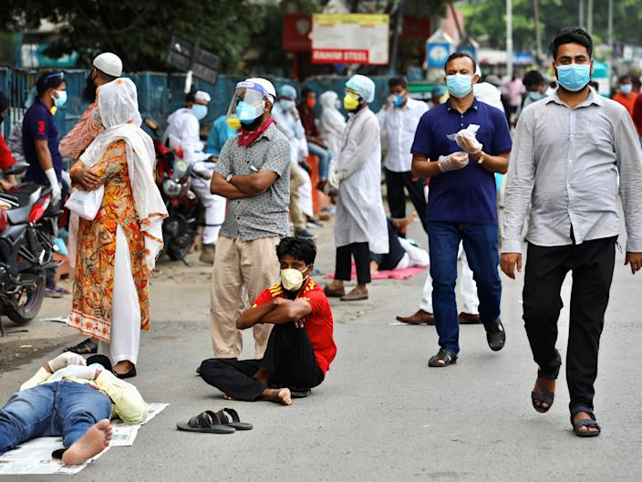 """People wait in the queue outside of a coronavirus testing center in Dhaka. <p class=""""copyright"""">Reuters</p>"""
