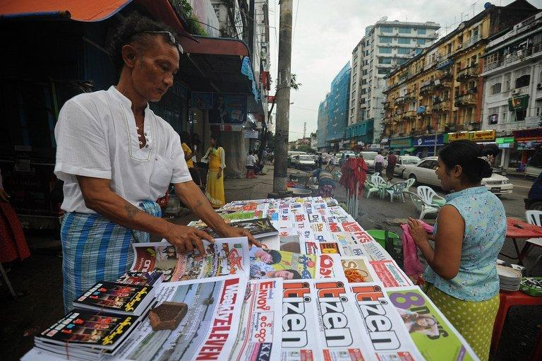 A vendor (L) sells local journals and newspapers on a roadside in Yangon on August 20, 2012