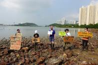 Lance Lau, 11, Elise Hon, 11, Rose Netherton, 36, and other climate activists hold placards as they pose for pictures during a climate strike and a beach clean-up at San Tau Beach on Lantau island in Hong Kong