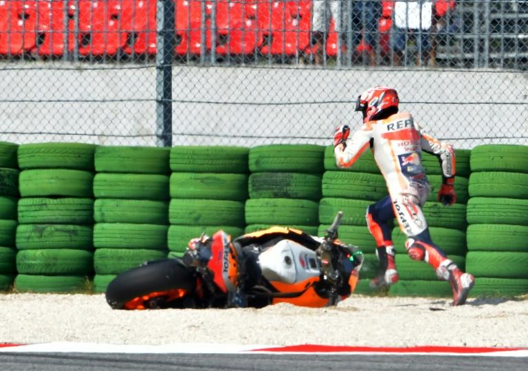 Spanish world champion Marc Marquez races to find a spare bike after falling in qualifying for the San Marino MotoGP Grand Prix