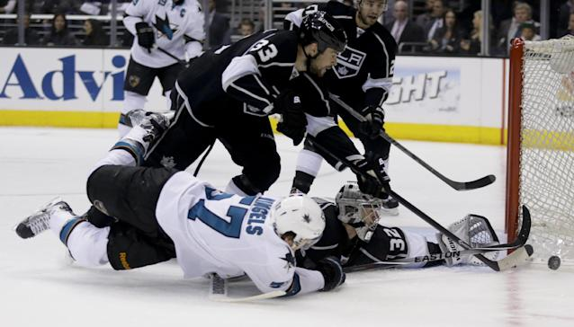 Los Angeles Kings goalie Jonathan Quick (32) blocks shot by San Jose Sharks center Tommy Wingels as Willie Mitchell looks on during the first period in Game 4 of an NHL hockey first-round playoff series in Los Angeles, Thursday, April 24, 2014. (AP Photo/Chris Carlson)