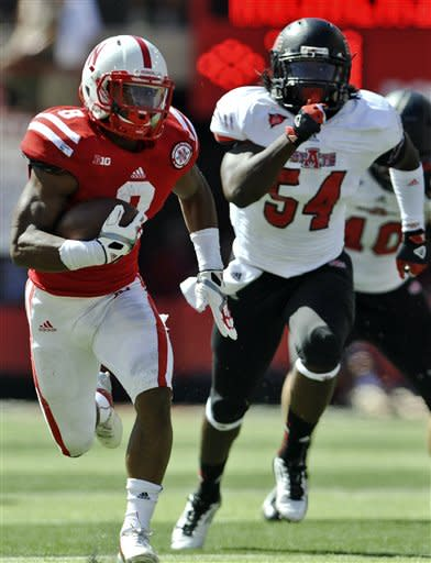 Nebraska's Ameer Abdullah (8) runs the ball as Arkansas State's Shervarius Jackson (54) pursues during the first half of an NCAA college football game in Lincoln, Neb., Saturday, Sept. 15, 2012. (AP Photo/Dave Weaver)