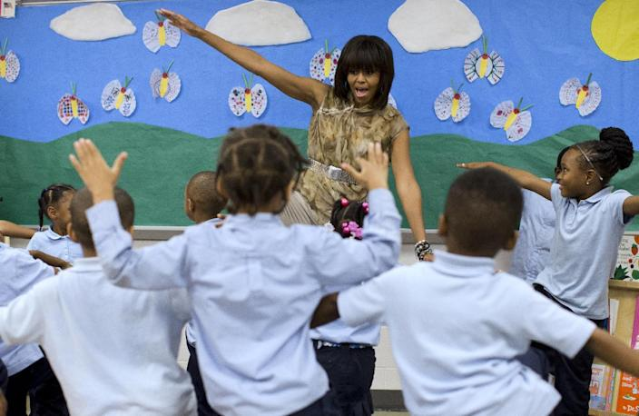 FILE - In this May 24, 2013 file photo, first lady Michelle Obama dances with a pre-Kindergarten class at Savoy Elementary School in Washington. The Savoy School was one of eight schools selected last year for the Turnaround Arts Initiative at the President's Committee on the Arts and Humanities. Turnaround Arts Schools use the arts as a central part of their reform strategy to improve low performing schools By reaching beyond the pair of relatively safe issues she has pushed _ reducing childhood obesity and rallying public support for military families _ the Harvard-trained lawyer who some say has played it safe is showing a willingness to step outside of her comfort zone. (AP Photo/Evan Vucci, File)