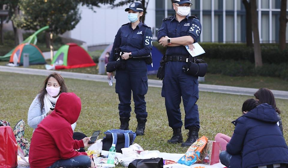 Government officers stand watch at a picnic area frequented by domestic helpers, amid social-distancing rules in place. Photo: Jonathan Wong