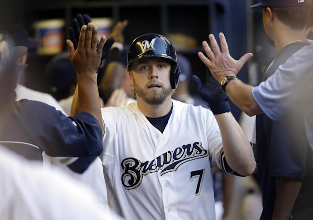 Milwaukee Brewers' Mark Reynolds is congratulated in the dugout after hitting a two-run home run during the fifth inning of a baseball game against the Minnesota Twins Monday, June 2, 2014, in Milwaukee. (AP Photo/Morry Gash)