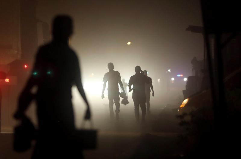 Locals walk on a street in Tarkwa, Ghana. (Photo: Siphiwe Sibeko/Reuters)