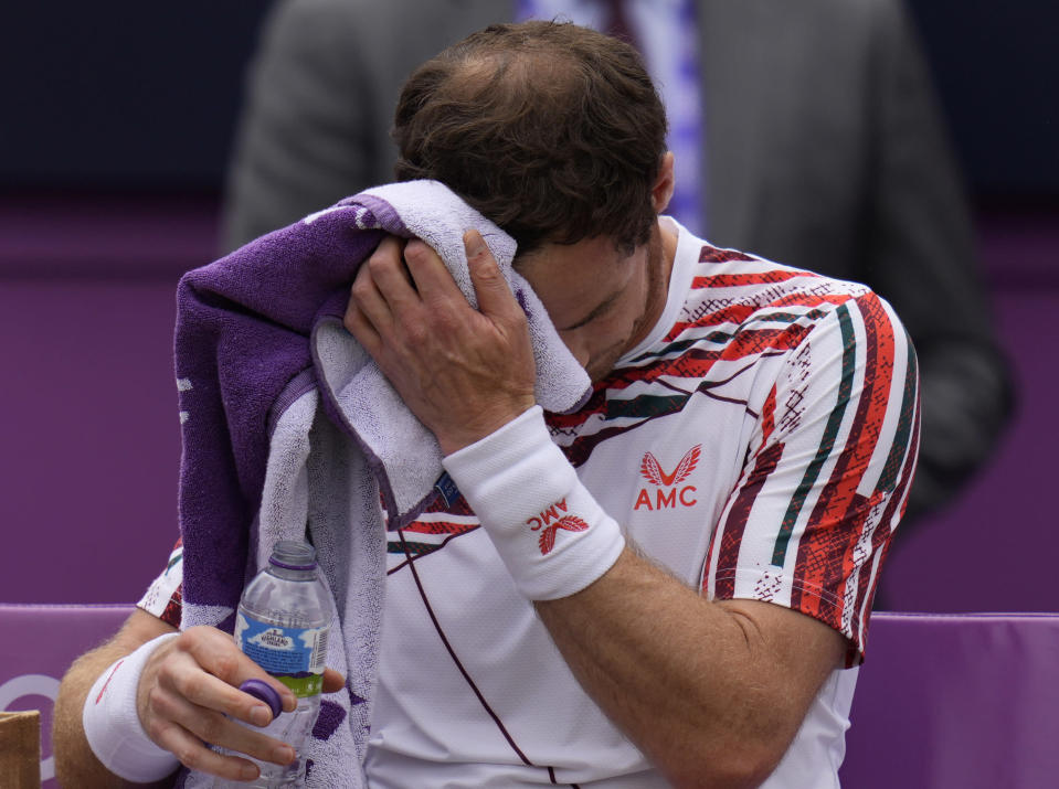 Andy Murray of Britain wipes his face during a break as he plays Matteo Berrettini of Italy during their singles tennis match at the Queen's Club tournament in London, Thursday, June 17, 2021. (AP Photo/Kirsty Wigglesworth)