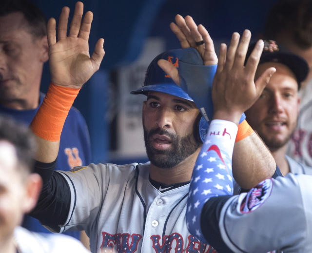 New York Mets' Jose Bautista is congratulated in the dugout after he scored on a two-run home run by Asdrubal Cabrera in the first inning of a baseball game against the Toronto Blue Jays on Tuesday, July 3, 2018, in Toronto. (Fred Thornhill/The Canadian Press via AP)