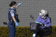 A police officer gestures to a customer to leave outside a supermarket in Auckland, New Zealand, Saturday, Sept. 4, 2021.vNew Zealand authorities say they shot and killed a violent extremist, Friday Sept. 3, after he entered the supermarket and stabbed and injured six shoppers. Prime Minister Jacinda Ardern described Friday's incident as a terror attack. (AP Photo/Brett Phibbs)