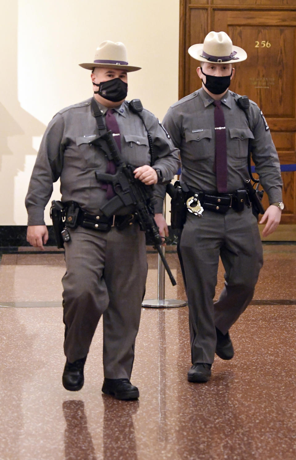 New York state Police patrol the hallways of the state Capitol prior to a planned President Trump protest rally ahead of the inauguration of President-elect Joe Biden and Vice President-elect Kamala Harris Sunday, Jan. 17, 2021, in Albany, N.Y. (AP Photo/Hans Pennink)