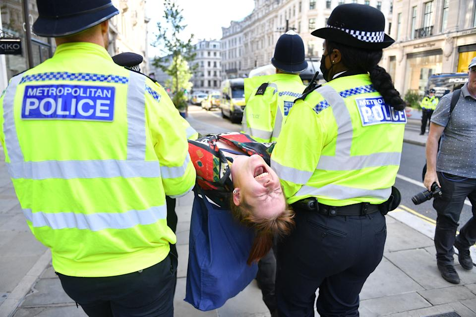 A climate activist from the Extinction Rebellion group is escroted away by police officers from a demonstration blocking the road in the middle of Oxford Circus in central London on August 25, 2021 during the group's 'Impossible Rebellion' series of actions. - Climate change demonstrators from environmental activist group Extinction Rebellion continued with their latest round of protests in central London, promising two weeks of disruption. (Photo by JUSTIN TALLIS / AFP) (Photo by JUSTIN TALLIS/AFP via Getty Images)