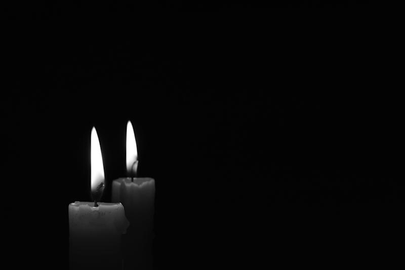 Light candle burning brightly in the black background. Candle flame. Black and white photo. There's room for your text. The concept of mourning, grief or sorrow.