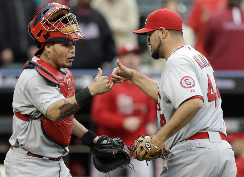 St. Louis Cardinals catcher Yadier Molina (4) celebrates the Cardinals 2-1 victory over the New York Mets with relief pitcher Edward Mujica (44) after a baseball game in New York, Thursday, June 13, 2013. (AP Photo/Kathy Willens)