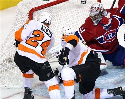 Philadelphia Flyers right wing Wayne Simmonds (17) scores the third goal against Montreal Canadiens goalie Carey Price (31) as teammate Matt Read (24) looks on during second-period NHL hockey game action on Thursday, Dec. 15, 2011, in Montreal. (AP Photo/The Canadian Press, Ryan Remiorz)