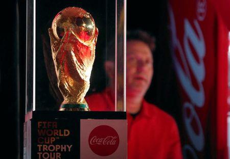 FILE PHOTO:  A man stands beside the FIFA soccer World Cup trophy displayed during a public celebration as part of a global tour in Cairo