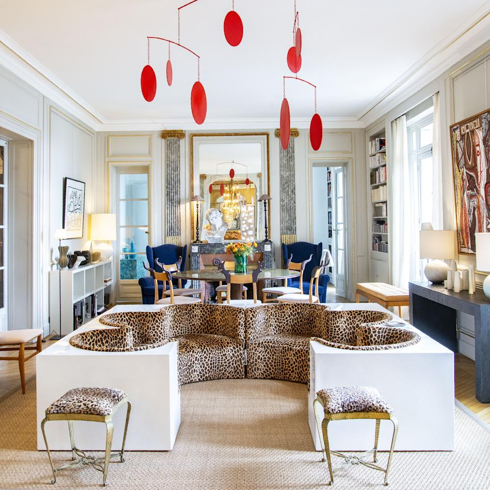 """<div class=""""caption""""> The main salon was decorated in the 1950s by the decorating firm Maison Jansen. The large white and animal print safari sofa is by the Italian design studio Archizoom from 1968. The iron stools are by Italian designer Pier Luigi Colli circa 1950. The ceiling mobile is by British artist Marc Cavell. In the background is a dining room table by Italian architect Carlo di Carli, and the armchairs are by Christian Lacroix. </div>"""