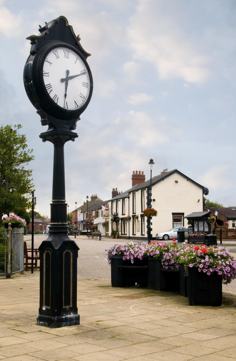 Freckleton Village and clock in Lancashire, with flower display and public house