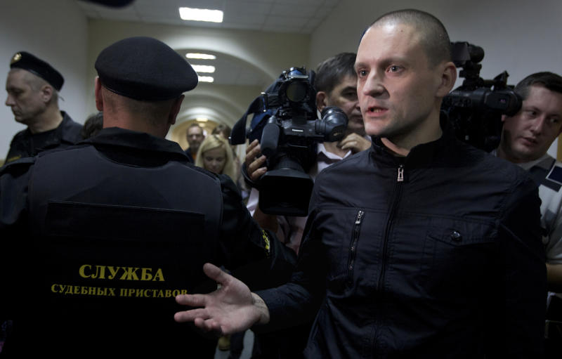 Opposition leader Sergei Udaltsov, right, speaks to the media during a trial of his assistant, leftist activist Konstantin Lebedev in Moscow, Thursday, Oct. 18, 2012. Russia's top investigative agency filed criminal charges Thursday against Konstantin Lebedev, an assistant of opposition leader Sergei Udaltsov, continuing a widespread crackdown on the movement against President Vladimir Putin. The Investigative Committee said in a statement that Left Front member Konstantin Lebedev has been charged with plotting mass riots and could face a jail term of up to ten years. (AP Photo/Ivan Sekretarev)