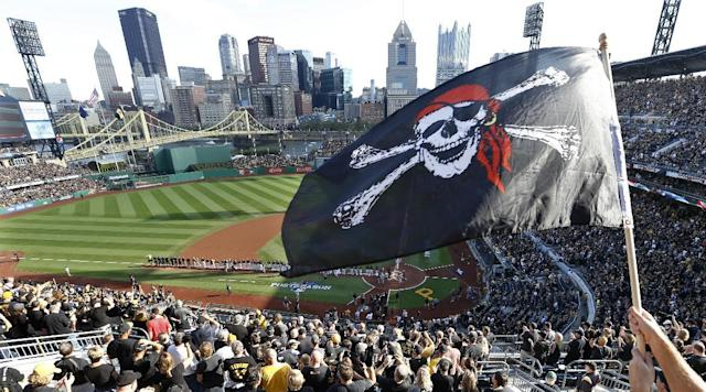 The city skyline is seen beyohnd the outfield walls of PNC Park as a Pittsburgh Pirates fan waves a Jolly Roger flag while the players are introduced before game 3 of a National League baseball division series between Pittsburgh Pirates and the St. Louis Cardinals on Sunday, Oct. 6, 2013, in Pittsburgh . (AP Photo/Keith Srakocic)