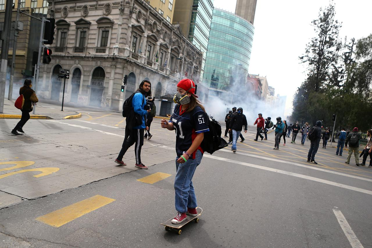 A demonstrator rides a skateboard during clashes at a march called by students to request changes in the education system in Santiago, Chile September 5, 2017. REUTERS/Ivan Alvarado