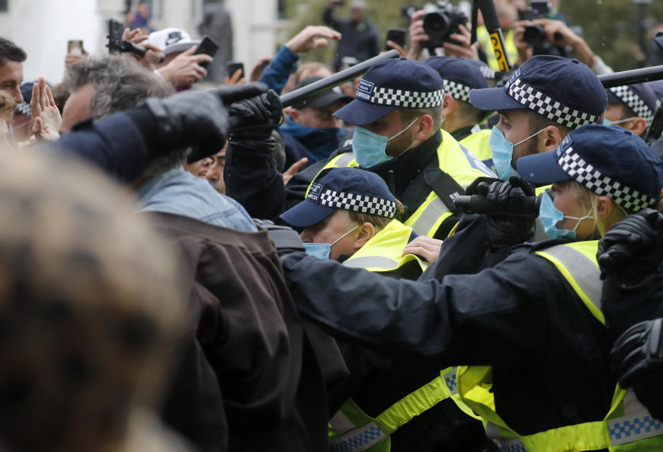 Riot police face protesters who took part in a 'We Do Not Consent' rally at Trafalgar Square, organised by Stop New Normal, to protest against coronavirus restrictions, in London, Saturday, Sept. 26, 2020. (AP Photo/Frank Augstein)