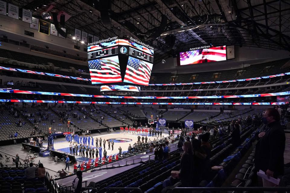 The Dallas Mavericks and Atlanta Hawks, along with a limited fan attendance, stand during the playing of the national anthem before the first half of an NBA basketball game in Dallas, Wednesday, Feb. 10, 2021. (AP Photo/Tony Gutierrez)