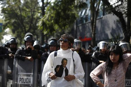 A demonstrator holds up a picture of leftist leader Andres Manuel Lopez Obrador, who is recovering from a heart attack at a hospital, in front of riot police during a protest against an energy reform bill outside the Senate building in Mexico City December 4, 2013. REUTERS/Tomas Bravo