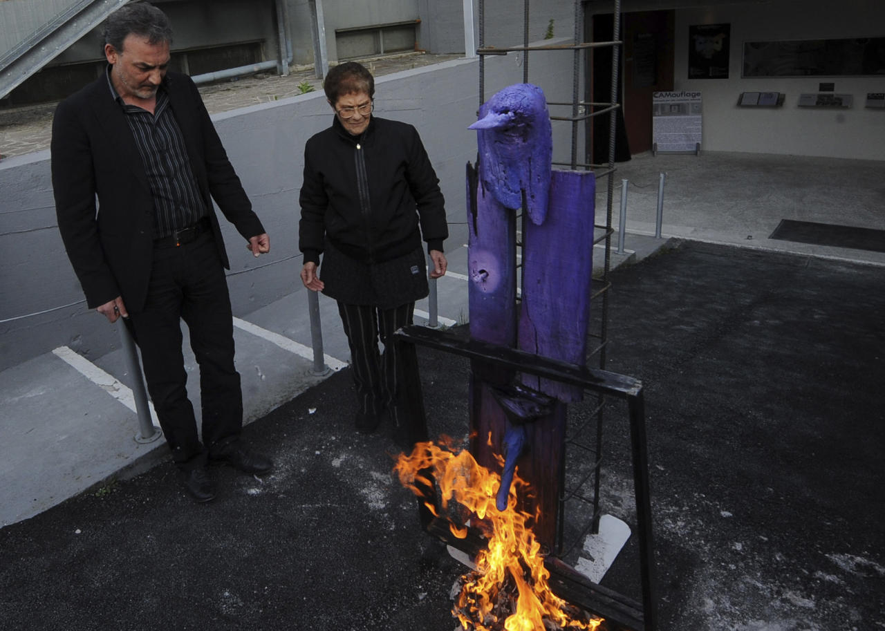 Antonio Manfredi, left, director of the Casoria Contemporary Art Museum, and Italian artist Rosaria Matarese burn one of Matarese's creations in front of the museum, near Naples, Italy, Wednesday, April 18, 2012. Manfredi is burning paintings to protest a shortage of funds. Italy's museums have been strapped for funds for decades, but art world officials say the economic crisis has aggravated the plight. (AP Photo/Franco Castano)